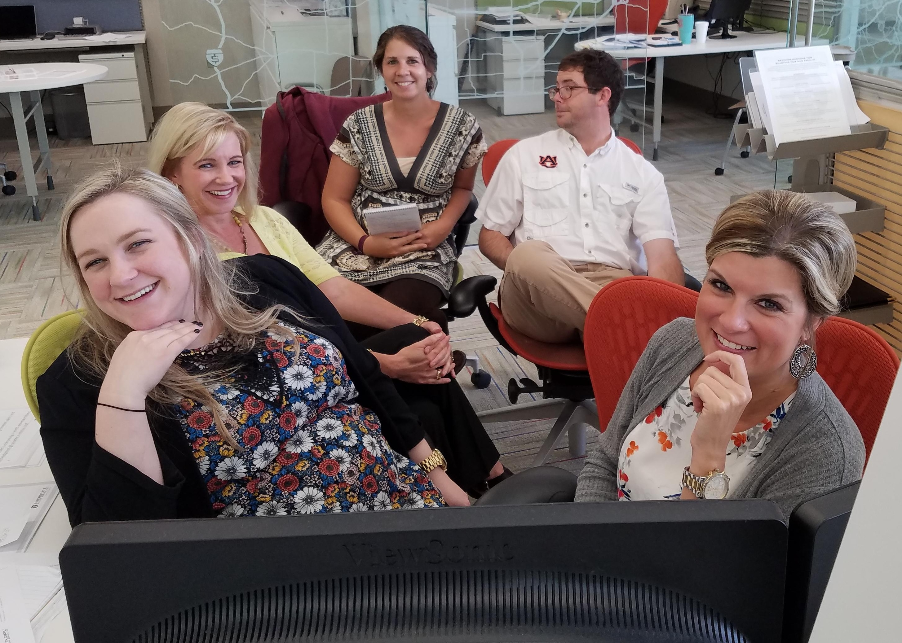 IBS Client Relations team members gathered at computer workstation