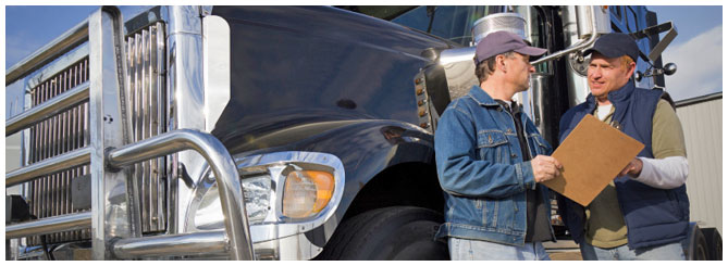 Two men discussing a form on a clipboard while standing in front of a black semi truck