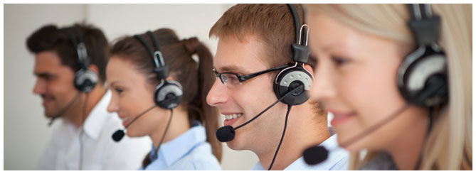 Row of customer service reps smiling with their headsets on