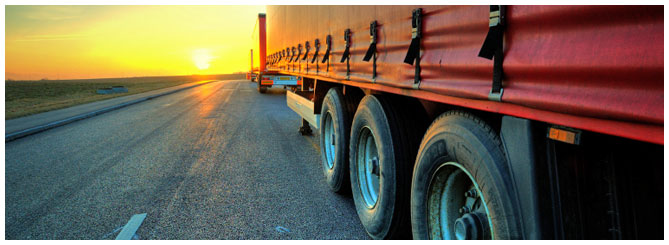Large Truck Trailer lined up on the highway facing the sunset